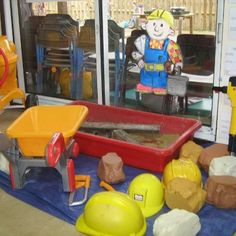 Exploring builders yard. Help mix cement, using sand and water and have fun transferring the big boulders in the wheelbarrow, and using all of the tools. The experience supports childrens UW as they role play different occupations, and their Expressive Arts and Design as they make-believe and pretend. By Sunny Socks Nursery School Ltd