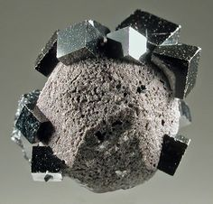 Bixbyite crystals on a garnet crystal which has been pseudomorphed by hematite. Collected John Holfert Geology Wonders