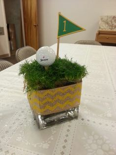 Something for a golf-themed party. Turf (or cut wheat grass) vase, ball, tee and flag number. Sports Centerpieces, Golf Party Decorations, Decoration Table, Party Themes, Centerpiece Ideas, Party Ideas, Event Themes, Banquet Centerpieces, Grass Centerpiece