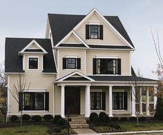 Hardie siding, farmhouse exterior, black shutters, wood door,