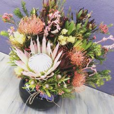 Native Inspiration from Simply Stems, beautiful Black fish bowl with King Protea, leaucaspernum, succulent flowers