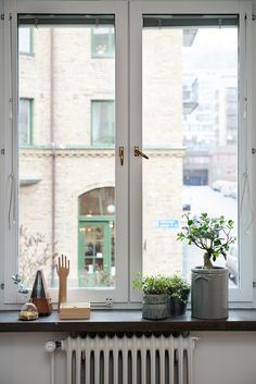Beautifully decorated windowsill: green plants and small personal objects. From Scandinavian style Gothenburg apartment.