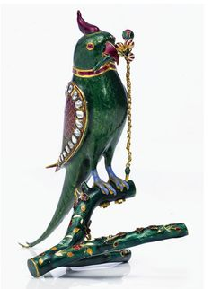 An Indian Gold, Enamel, and gem-set parrot-form scent bottle, early 20th century. The parrot perched on a forked branch, a spray of berries and bud in its beak and chain stopper for dispensing scent, with calibré ruby collar,  with crest-form screw-on cover, all decorated with translucent emerald green and scarlet enamel on a chased feather ground, the wings set with a border of faceted white sapphires, apparently unmarked.