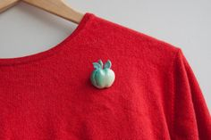 Vintage Apple Brooch pinned on a red sweater > Sold by broesj via Etsy, €5.00