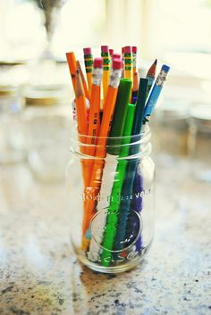 mason jar with various shades of blue and orange colored pencils for guests to sign the matting of a picture frame