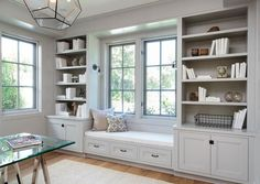 Well appointed gray office features a built in gray shelves accented with gray…