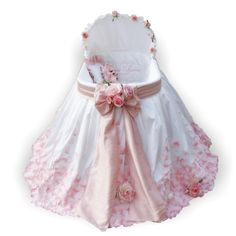 This is a bassinet that is *truly* 'fit for a princess'. Made out of silk dupionni, with net tulle....1500 silk rose petals sewn on (by hand).....monogrammed inside the bed with babies full name....the big silk bow tied all around. It's amazing! Oleyna Boyko Rose Petals Silk Dupionni Bassinet Set www.thepepperkids.com