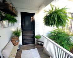 Love all things on this cute little porch. Pail planters and old tool box planter with bench and black door.