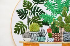 This larger embroidery hoop is my plant wish list! It depicts several different plants, each in a fun planter. Its the perfect addition to your indoor garden or the the perfect alternative!  All of my embroidery hoop art pieces are original designs and meticulously hand stitched. I emphasize clean, contemporary design while maintaining affordable prices, creating accessible and unique art for the home!  This hoop is 12 inches in diameter and was made using embroidery floss on stretched…