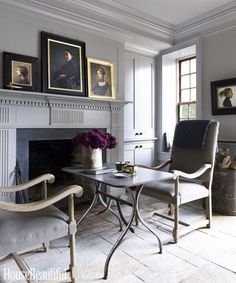A fireside table is the perfect setting for reading or a casual supper for two. The entire interior of the Charleston rental was painted in Sherwin-Williams's Pussy Willow. The contemporary portraits by Paula Rubino and Charles Weed were purchased from Ann Long Fine Art in Charleston. Click through for more of the best living room decorating ideas and designs.
