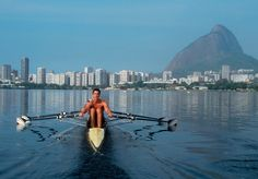 Rowing, Rio de Janeiro, Brazil, South America, Elite rowers from the Vasco de Gamma Rowing Club row on the Lagoa toward the highrises of Ipa...