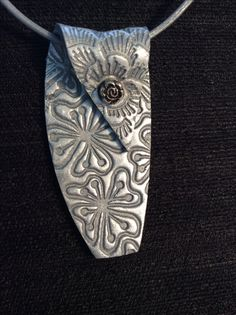 Textured silver clay pendant, folded over a silver leather thong. Easy.com/shop/DWDesigner.