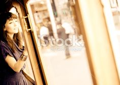 Beautiful woman longingly looking out a window Royalty Free Stock Photo