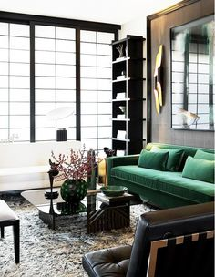 Modern living room with green sofa and floor-to-ceiling windows