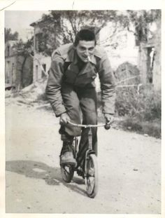 1944- U.S. Cpl. Jim Ross riding a child's bicycle down a street in the captured city of Scauri, Italy.
