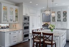 white crisscross cabinets, light countertops, dark wood floor, stacked appliances, light fixtures