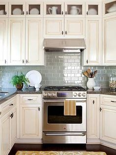 Coupled with stainless-steel appliances, the glass tile backsplash maintains a cool veneer in this traditional white kitchen. The reflective quality of the sage green tile helps blur the line between the modern appliances and traditional off-white cabinetry and espresso-color wood floors.
