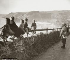 A GI stands guard as children watch invasion craft practise at Slapton, Devon. Max Arthur'...