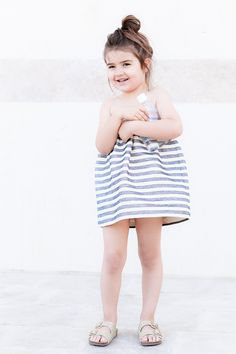 Kid style: Miss Kaira wearing Douuod striped skirt as dress, gold glitter Mayoral sandals, and A6 memobottle water bottle.