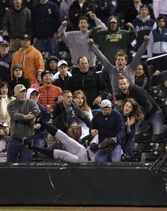 Detroit Tigers' Don Kelly tumbles into the crowd after catching a foul ball hit by Seattle Mariners' Jesus Montero for the final out in the ninth inning of a baseball game, Tuesday, May 8, 2012, in Seattle. The Tigers beat the Mariners, 6-4.
