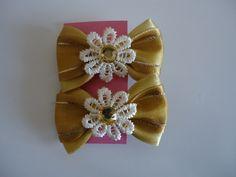 Lacinhos dourados e flor pérola com pedra no bico de pato. R$ 12,00