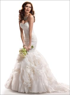 Maggie Sottero 'Primrose'  Description: Understated, yet rich in design, this tulle and Chic Organza fit and flare features a slimming ruched bodice, with a textured swirling rosette skirt. Finished with strapless, sweetheart neckline and signature corset back closure. Division: Memories  $998.00