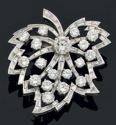 """VAN CLEEF & ARPELS     Clip """"leaf""""   platinum set with diamonds and baguette cut diamonds accented with modern amenities including a diamond largest center. Signed Van Cleef and Arpels NY and numbered.   central diamond weight: 1.75 carats approx   14 K gold Pin"""