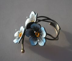 Ring made of silver 930 and natural leather. Flowers nots handpainted waterproof and abrasion resistant paint, finished with decorative veins. Silver oxidized to the colors of brown and gold. Ring is easy to adjust, suitable for each size of a finger.
