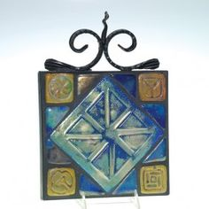 Pewabic Pottery tile tableau consisting of 13 luster tiles, 8 triangular with no design, four 1 3/4 inch tiles with designs and a single 5 1/2 inch tile with a four lobe design, assembled into an 8 1/4 inch square and cemented into place with black grout. The ceramic portion is contained within a wrought iron frame.
