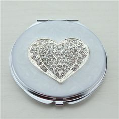 Diamonds heart compact mirror This elegant crystals heart decor compact mirror is a perfect gift for lady. It is covered with white enamel glaze and mounted with bling-bling crystals and elegant pearls. There are two mirrors inside. One regular mirror on top, the other 2x magnifying mirror on bottom. We can also make 3x magnifying mirror as per your request.