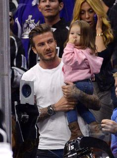 Retired soccer player David Beckham holds his daughter Harper as he watches the Los Angeles Kings play the San Jose Sharks in Game 7 of the Western Conference semifinals in the NHL hockey Stanley Cup playoffs, in Los Angeles on Tuesday, May 28, 2013,. (AP/Mark J. Terrill)