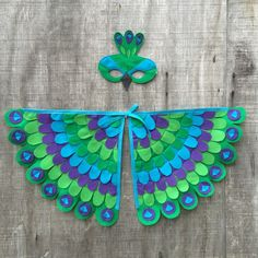 Pavoneándose alrededor del jardín con plumaje maravilloso! Muy divertido, la aleta y la aventura de este colorido traje!   Artísticamente elaborado con fieltro Eco-Fi, un hermoso fieltro made in USA de botellas de plástico recicladas (yay! impresionante!) Alas tienen hombros elásticos (va en como una mochila) y los elásticos de la muñeca, pulgar en las extremidades. El espacio entre las alas es ajustable para crecer con su niño. Cosido con cuidado, crear un juguete resistente a pasado por…