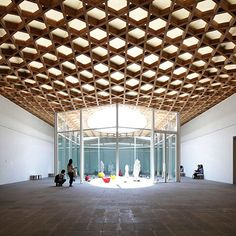 inside shigeru ban's 'oita prefectural art museum', in japan. described as a museum of the five senses and encounters, the woven timber façade, references the traditional bamboo crafts also shown inside where the gridshell roof structure spans internal volumes. #shigeruban #architecture