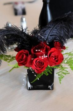 Black feathers and red roses :) i would loveeee these for center pieces!.....maybe with white feathers?