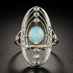 Reminiscent of an armillary sphere, this celestial jewel, dating back to the first or second decade of the twentieth century, centers on an earth-like opal elliptically orbited by twinkling diamonds. Lightly hand fabricated in platinum over gold, this unique and enchanting dinner ring measures a striking 1 inch long. Currently ring size 5 3/4+.