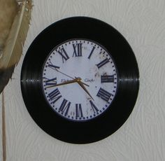 """Klicknc Photo-on-Vinyl Wall Clock. Made from a 12"""" vinyl LP record, this clock features a glossy photo of an """"aged"""" rusty clock face. It is adorned with gold-coloured aluminium arrow-style hands.   The battery operated ticking EZ Quartz® Clock Movement carries a 12 month guarantee and includes a built-in hanging hook. Both the Clock Movement and the hands are RoHS approved. Requires 1 x AA Battery (Not Included)."""