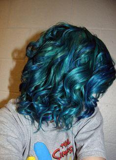Peacock green-blue curly short hair.