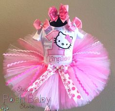 Pink Hello Kitty is a Super Cute Tutu Birthday Outfit for Your little girl who will look so beautiful for her birthday photos in this adorable Outfit! She Will Be the Star of the Show!   This Girls Personalized Birthday Tutu Outfit comes with the Tutu, Embroidered and Personalized Onesie/Shirt and a Matching Ribbon Bow on Headband with Clip or 2 Mini Bows on Clips for a extra Fee.   All Tutus Are Made with High Quality Diamond Weave Cut Shimmer Wedding Tulle Fabric.   All the Extra Frilly…