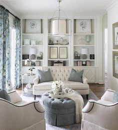 Modern coastal decorating style living room design featuring a white, cream, beige, gray, and blue color palette. The built-in bookshelves with a mix of art and objects makes this room special - Contemporary Beach House Decor & Ideas