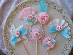 Gorgeous pink and aqua cupcake toppers combine paper lace, colored feathers, crepe paper, ribbon, and roses to make decorations beautiful enough for