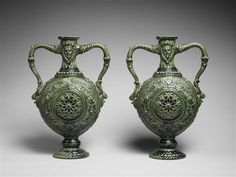 "Ceramists Greber Charles (1853-1935) and Greber Pierre (1896-1965). This pair of vases is inspired by the renaissance, the form is called ""gourd"" or ""canteen"". A green glaze covers the entire object, enhaussing the ornaments."