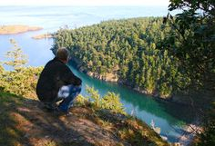 Best places to visit and hike in San Juan Island National Monument - hiker looks down on Lopez Island's Watmough Bay.