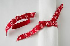 """A red ribbon with white snowflakes, tied around a napkin, makes an inexpensive and colorful Christmas accent which also acts as a napkin ring. This photo is from the iBook, """"White Dishes and Table Settings, Beauty on a Budget,"""" in the chapter on red and white snowflake themes, at the table and surrounding room."""
