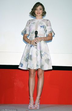 Perfection: Miranda Kerr looked demure in the fit and flare style with bell- sleeves, which also featured leaf-style lace detailing that flashed a hint of cleavage at a promotional appearance in Japan on Tuesday