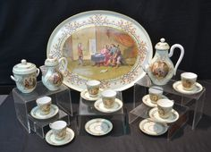 """HAND PAINTED RUSSIAN PORCELAIN TEA SET  CONSISTING OF LARGE (21"""" x 16 1/2"""") TRAY WITH INTERIOR MUSICAL SCENE SURROUNDED BY SCROLL WORK DECORATIONS , TEA POT , SUGAR & CREAMER (HAS HAIRLINE) WITH DOUBLE SIDED FIGURAL INTERIOR SCENE MEDALLIONS , (7) CUPS & (9) SAUCERS (ONE FLAKE) WITH ORIGINAL CARRY CASE WHICH HAS RUSSIAN CERTIFICATE DATED 1869 (TRAY IS INCISED 1815)"""