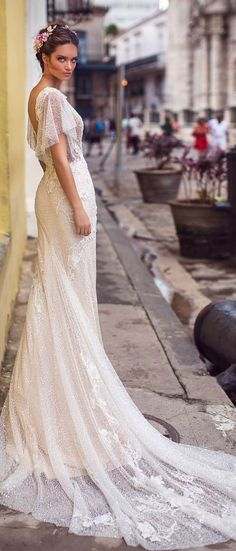 Exquisitely beaded Flora gown embodies romance and elegance. Beautiful train adorned with floral appliques lends this gown femininity short sleeves sheath wedding dress #wedding #weddingdress #weddinggown #bridedress