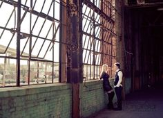 couple poses under broken steel windows at Jacksonville FL historic Ford Motor Company assembly plant