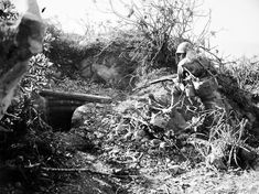 A Marine covers one of the entrances of a Jap cave awaiting the arrival of a flame thrower. Iwo Jima - March 3, 1945