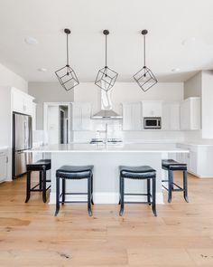 Modern white kitchen with traditional accents featuring light European oak hardwood floors, white subway tile backsplash, white quartz countertops, stainless range hood, custom white shaker cabinetry, modern geometric pendant lights, and gray walls