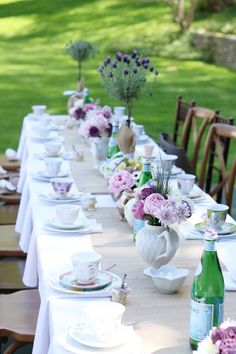 Mothers Day Garden tea party table decor setting with tea cups and tea pots with flowers. Simple outdoor garden tea party decorations || Darling Darleen